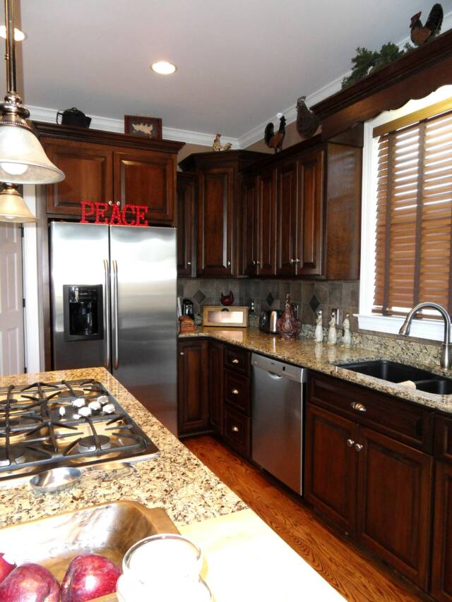 Dark stained cherry kitchen cabinets with crown and rope molding